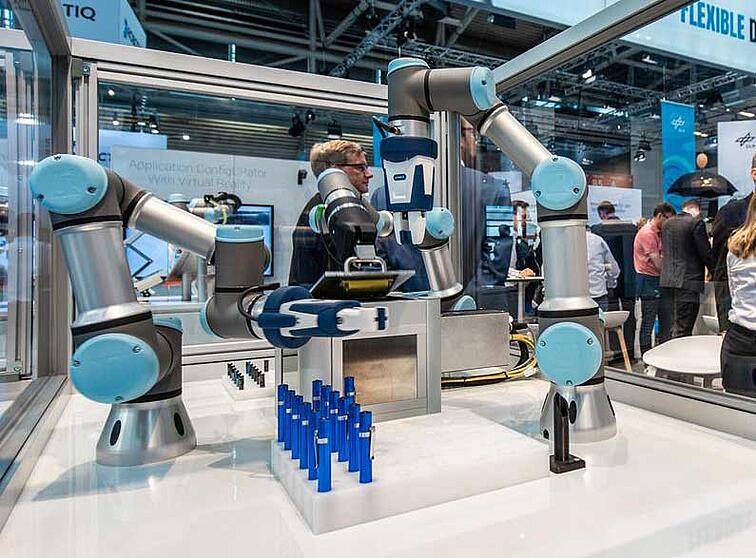Three-UR3e-robots-assemble-flashlights-that-are-then-handed-over-to-the-trade-show-visitors